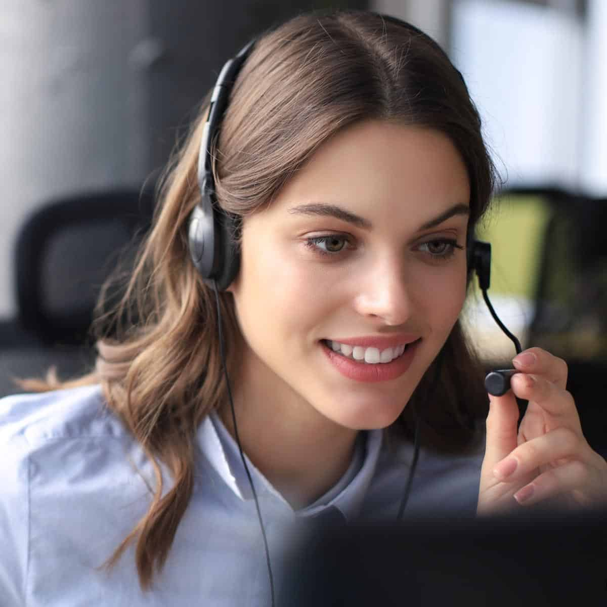 A customer service representation women wearing her headphone and making an outbound call